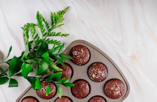 Gebackene schokoladen-brownies mit bestreuen und grünen zweigen.