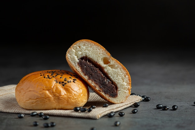 Gebackene schwarze bohnenpastenbrötchen auf braunen stoff legen