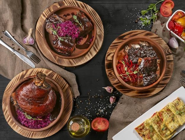 Gebackene schweinshaxe schweinebauch kalbsrippchen mit saucen und gemüse