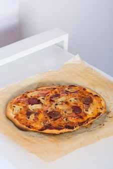 Gebackene selbst gemachte pizza auf pergamentpapier über der tabelle