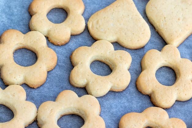 Gebackene shortbread-kekse in form von blumen und herzen auf einem backblech mit pergamentpapier, das gerade aus dem ofen genommen wurde. tee-snack zum frühstück. selektiver fokus. nahaufnahme draufsicht