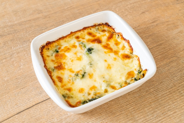 Gebackene spinatlasagne mit käse in weißer platte