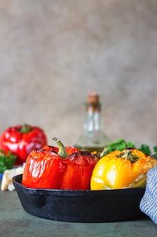 Gebackene süße paprika gefüllt mit hühnchen oder pute, mais und kräutern in gusseiserner pfanne.