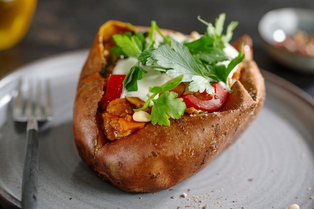 Gebackene süßkartoffel mit sauerrahm und bohnen mit petersilie auf teller serviert. nahaufnahme.