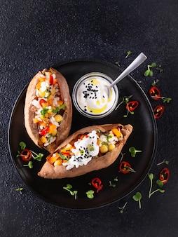 Gebackene süßkartoffel oder yam gefüllt mit kichererbsen, reis, gemüse, paprika und joghurtsauce