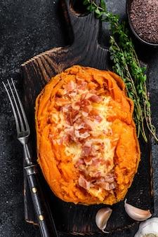 Gebackene süßkartoffel-yams gefüllt mit hackfleisch und käse. schwarzer hintergrund. ansicht von oben.