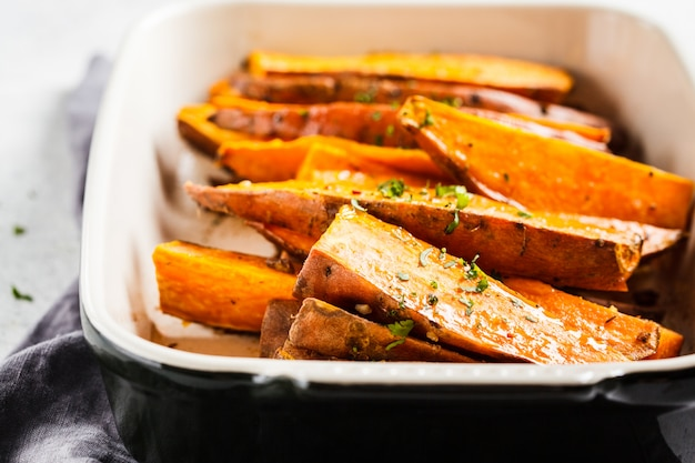 Gebackene süßkartoffelscheiben mit gewürzen im ofenteller. gesundes veganes lebensmittelkonzept.