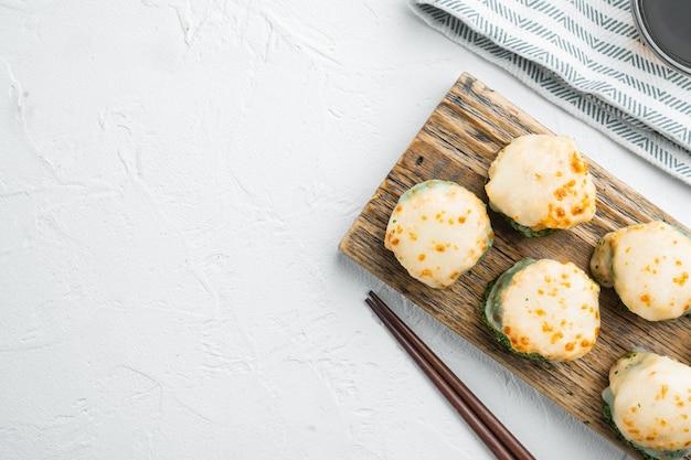 Gebackene sushi-maki-rollen mit lachs, krabben, gurken, avocado, flugfischrogen und würziger soße, auf weißem steintisch, draufsicht flach