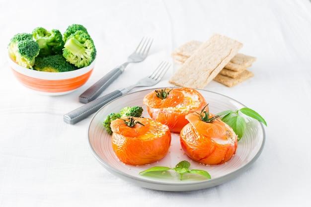 Gebackene tomaten mit ei, brokkoli und basilikumblättern auf einem teller und einer schüssel frischem brokkoli. diät-mittagessen