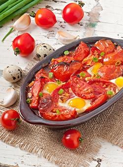 Gebackene tomaten mit knoblauch und eiern mit frühlingszwiebeln dekoriert