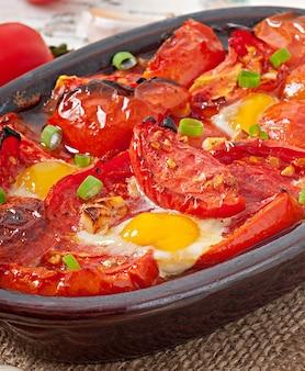 Gebackene tomaten mit knoblauch und eiern mit frühlingszwiebeln dekoriert Kostenlose Fotos
