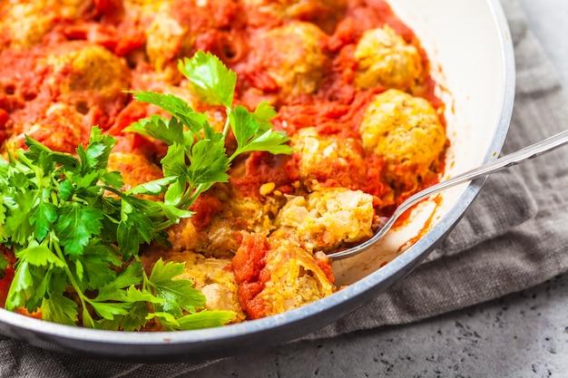 Gebackene vegane bohnenfleischbällchen in tomatensauce in der pfanne.