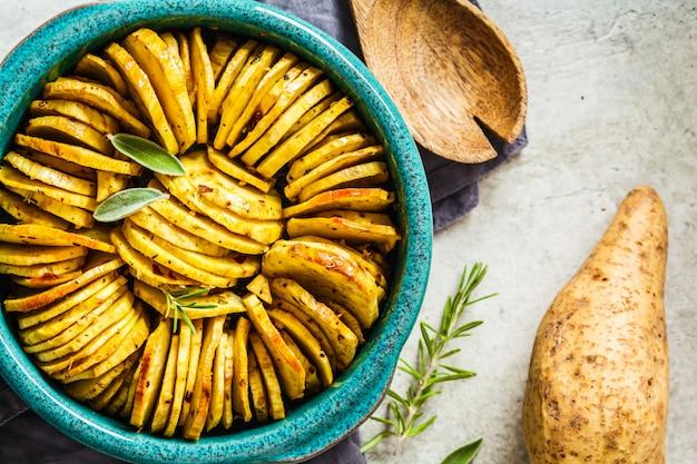 Gebackene weiße süßkartoffelkasserolle mit kräutern im blauen teller, draufsicht.