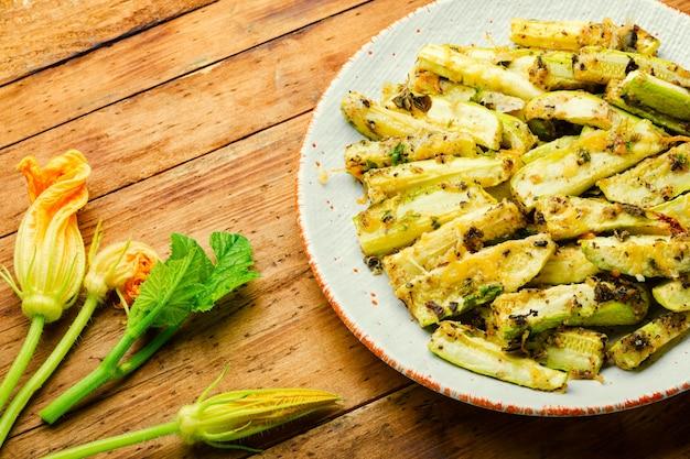 Gebackene zucchini mit gewürzen und kräutern. geröstete zucchini-sticks auf dem teller