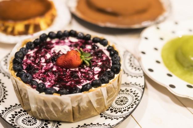 Gebackener blaubeerkäsekuchen mit erdbeere und grünem tee der unschärfe, schokoladenkuchen auf weißem holztisch. viele geburtstagstorten zum feiern.