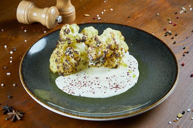 Gebackener blumenkohl in gewürzen und kräutern mit cremig-würziger sauce und olivenöl. gesundes, veganes essen. fitness-diät. restaurant serviert gerichte. garnierung. nahaufnahme