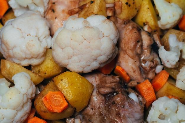 Gebackener blumenkohl mit karotten, kartoffeln und hühnerfleisch an. traditionelles hausgemachtes gesundes essen