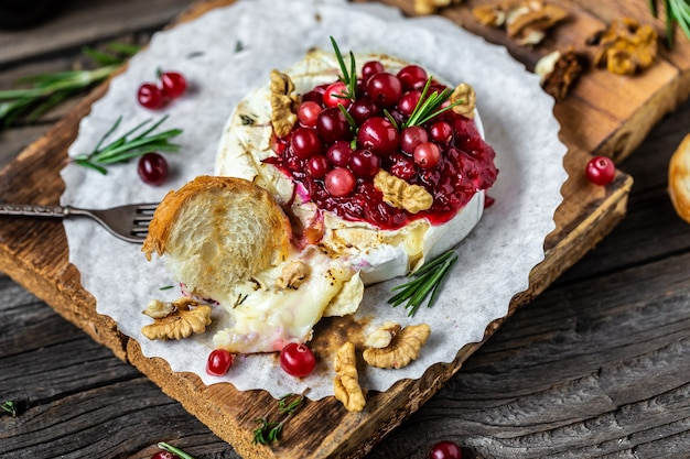 Gebackener camembert-brie mit frischer rosmarin-cranberry-sauce. gourmet-vorspeise.