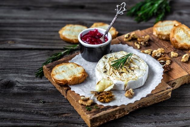 Gebackener camembert mit toast, rosmarin, preiselbeeren und nüssen auf rustikalem holztisch.