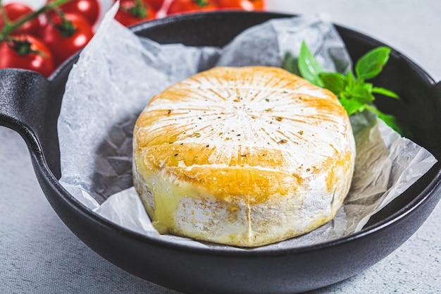 Gebackener camembert- oder brie-käse in einer schwarzen pfanne. Premium Fotos