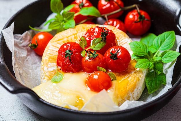 Gebackener camembert- oder brie-käse mit tomaten in einer schwarzen pfanne.