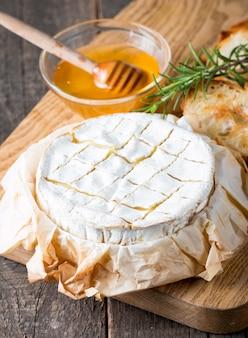 Gebackener camembert- oder briekäse auf einem hölzernen brett.