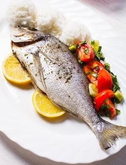 Gebackener dorado-fisch mit reis und salat auf dem weißen teller