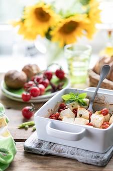 Gebackener feta-käse mit kirschtomaten mit basilikum und olivenöl. griechische nationale küche.
