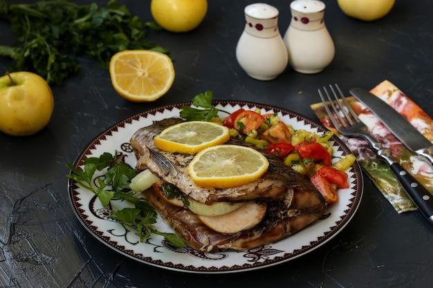 Gebackener fisch auf einem teller mit zitrone, salat und grüns. auf dem tisch liegen petersilie, zitrone, messer, gabel, salz und pfeffer.