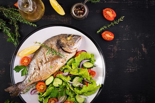 Gebackener fisch dorado mit zitrone und frischem salat in der weißen platte auf dunklem rustikalem hintergrund. ansicht von oben. gesundes abendessen mit fischkonzept. abnehmen und sauber essen