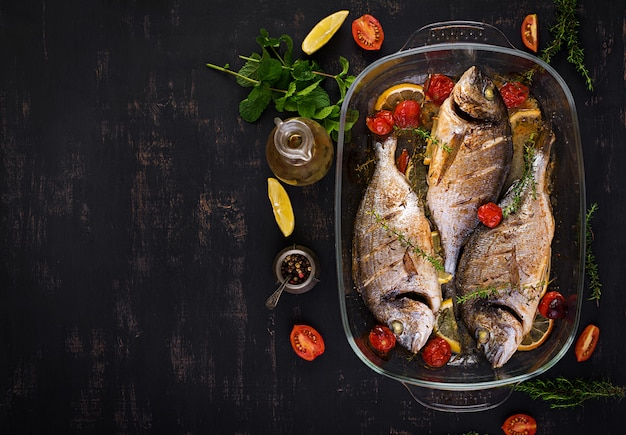 Gebackener fisch dorado mit zitrone und kräutern in der backform auf dunklem rustikalem hintergrund. ansicht von oben. gesundes abendessen mit fischkonzept. abnehmen und sauber essen