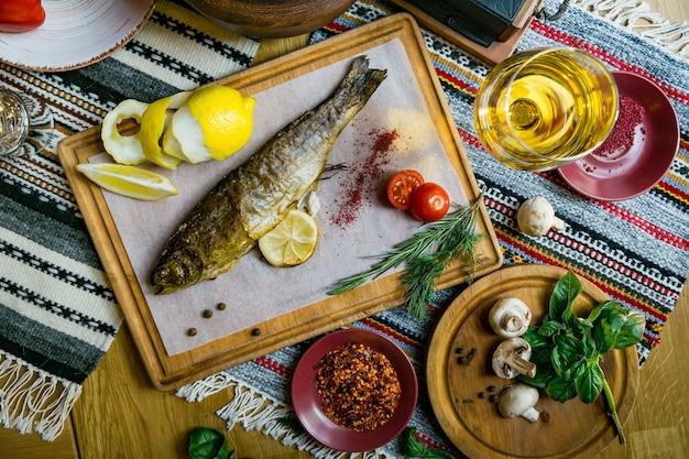 Gebackener fisch seebarsch mit fischgewürzen, wein und salat. gebackene meeresfrüchte im restaurant gesunde ernährung