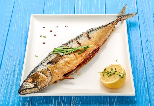 Gebackener ganzer fisch gegrillt auf einer platte mit gemüse und zitrone