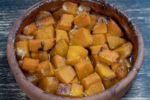 Gebackener gelber kürbis mit honig, olivenöl und gewürzen auf einem teller auf dem holztisch. vegetarisches essen. nahaufnahme