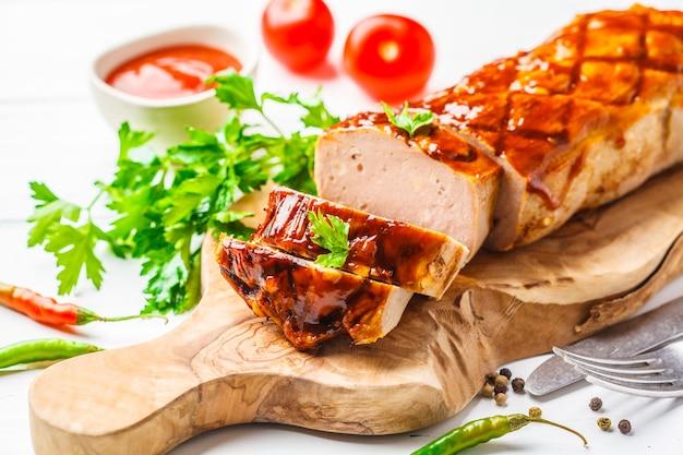 Gebackener hackbraten mit gemüse und barbecue-sauce auf einem holzbrett