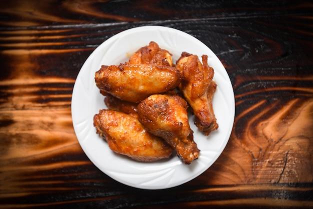 Gebackener hühnerflügel-grill auf heißem und würzigem huhn der platte auf dunkelheit