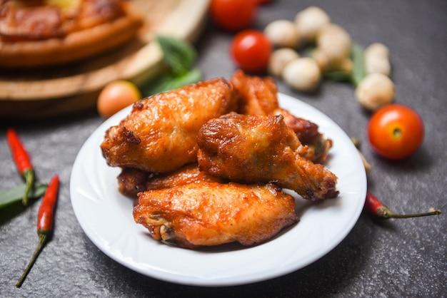 Gebackener hühnerflügel-grill auf platte, heißem und würzigem huhn und soße auf dunkelheit
