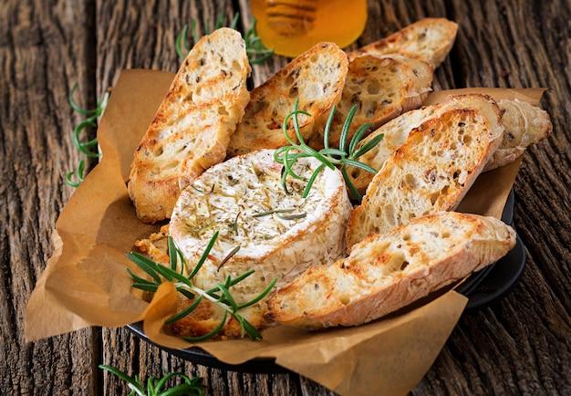Gebackener käsecamembert mit rosmarin und honig. leckeres essen.