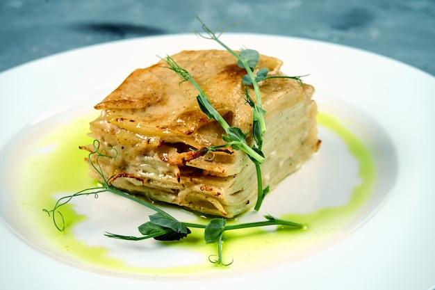 Gebackener kartoffelgratin mit sahne und käse in einer weißen platte auf beton