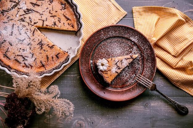 Gebackener kuchen in einer keramischen form besprüht mit schokoladenscheiben auf einem holztisch. stück kuchen auf lehmplatte gelegt und mit blume verziert