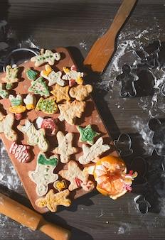 Gebackener lebkuchenmann, kekse in verschiedenen formen liegen auf einem holztablett. das konzept der neujahrstraditionen und des kochprozesses. kekse auf einem braunen holztisch. familienproduktion. hausbäckerei