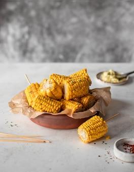 Gebackener mais mit knoblauchbutter auf einem grauen hintergrund