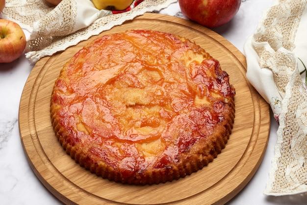 Gebackener runder apfelkuchen auf holzbrett und frischen äpfeln, draufsicht, weißer tisch