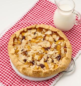 Gebackener runder kuchen mit apfelstücken, bestreut mit mandelflocken auf einem weißen tisch, ansicht von oben