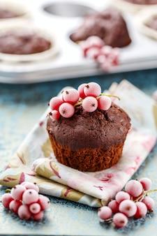 Gebackener schoko-muffin, mit gefrorenen zweigbeeren, rote johannisbeere, blaues textil, holztisch