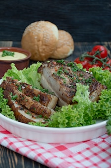 Gebackener schweinebauch mit gewürzen. geschnittene brust, serviert mit gemüse. traditionelles gericht der ukraine.