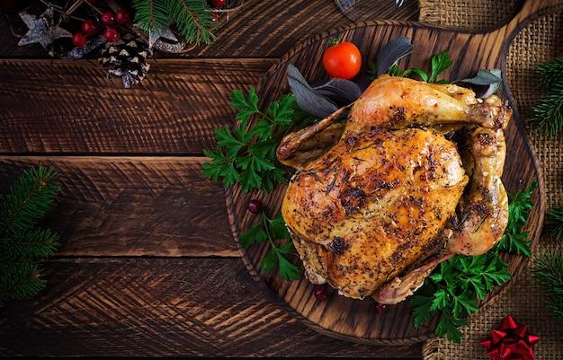 Gebackener truthahn oder huhn. der weihnachtstisch wird mit einem truthahn serviert, der mit hellem lametta dekoriert ist. brathähnchen, gedeck. weihnachtsessen. draufsicht, overhead, kopierraum
