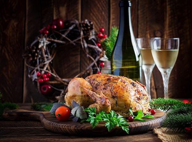 Gebackener truthahn oder huhn. der weihnachtstisch wird mit einem truthahn serviert, der mit hellem lametta dekoriert ist. brathähnchen, gedeck. weihnachtsessen.