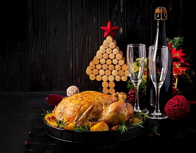 Gebackener truthahn oder huhn. der weihnachtstisch wird mit einem truthahn serviert, der mit hellem lametta dekoriert ist. brathähnchen, tisch. weihnachtsessen.