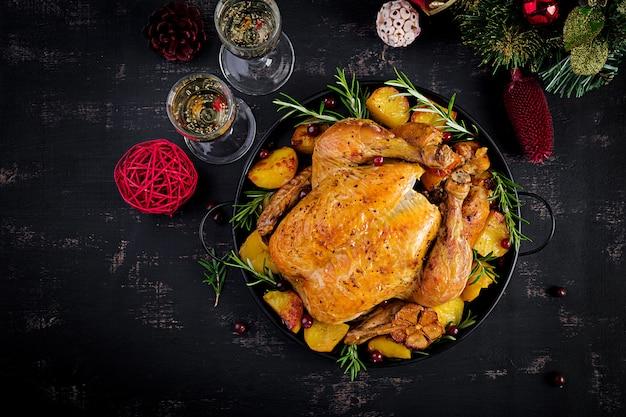 Gebackener truthahn oder huhn. der weihnachtstisch wird mit einem truthahn serviert, der mit hellem lametta dekoriert ist. gebratenes huhn. sitzordnung bei tisch. weihnachtsessen. ansicht von oben